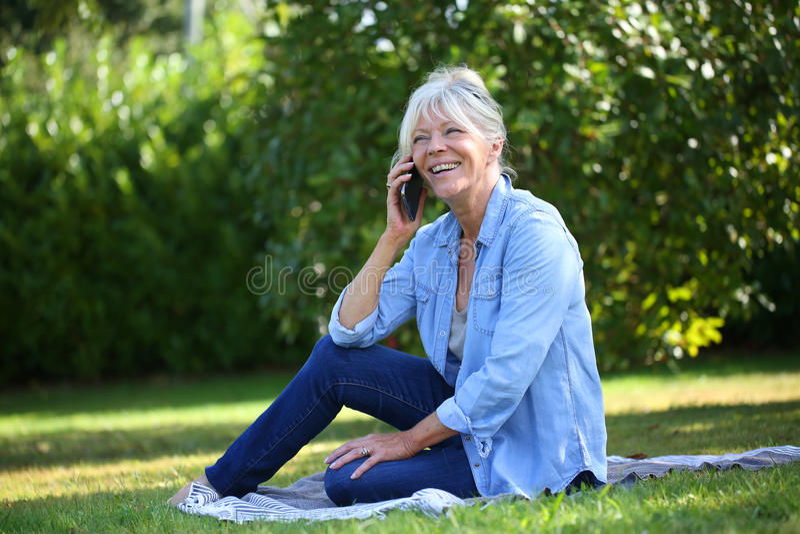 Gladlynt hög kvinna som sitter samtal ner på telefonen royaltyfri fotografi