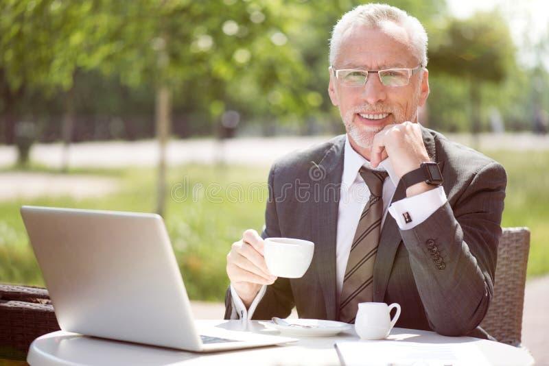 Gladlynt hög man som dricker kaffe royaltyfria foton