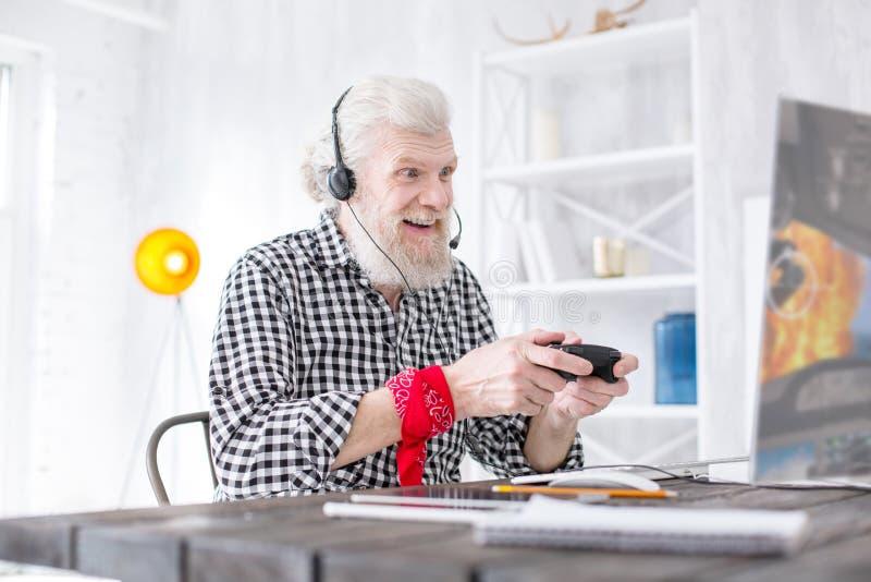 Gladlynt hög man som fokuseras på videospelet royaltyfri bild