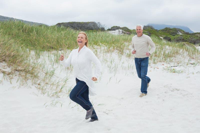 Gladlynt hög parspring på stranden arkivfoto