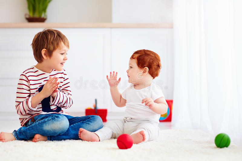 Gladlynt hög unge som hemma spelar med hans yngre litet barnbroder royaltyfri fotografi
