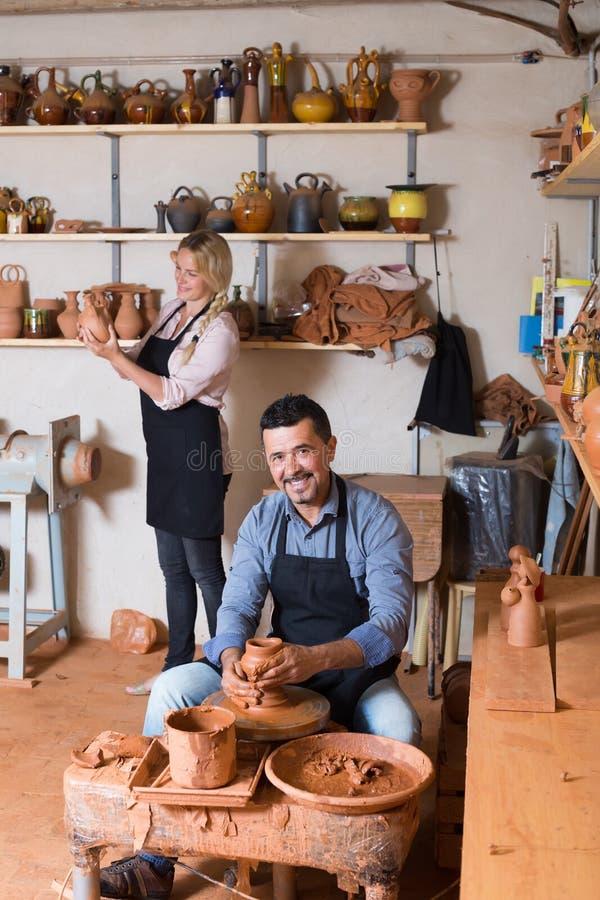 Gladlynt hantverkaredanandekruka genom att använda krukmakerihjulet royaltyfria foton