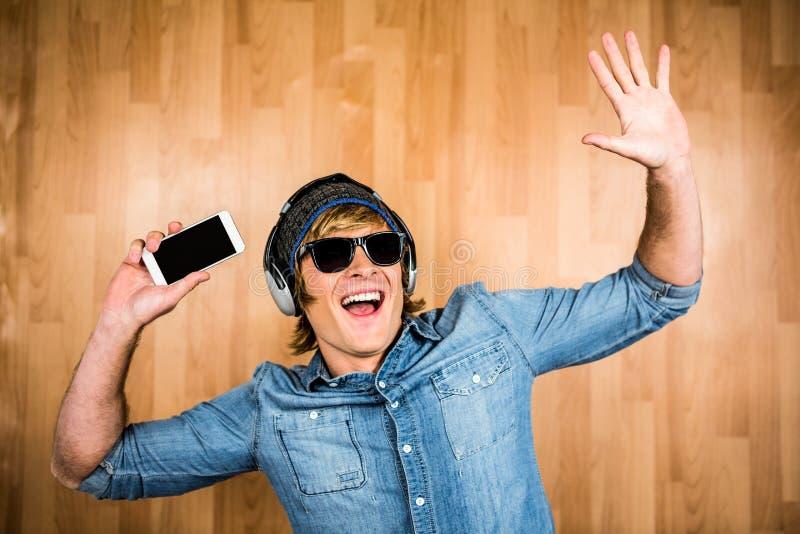 Gladlynt hipster som lyssnar till musik arkivfoto
