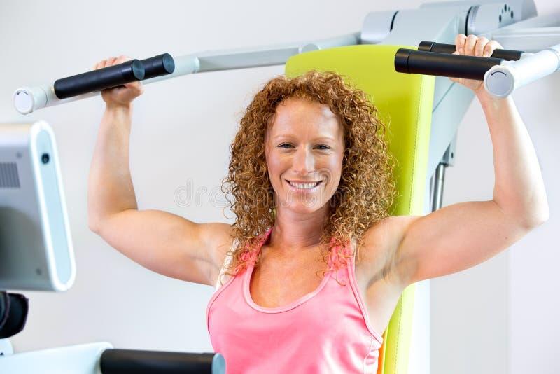 Gladlynt idrotts- kvinna som använder viktmaskinen arkivbilder