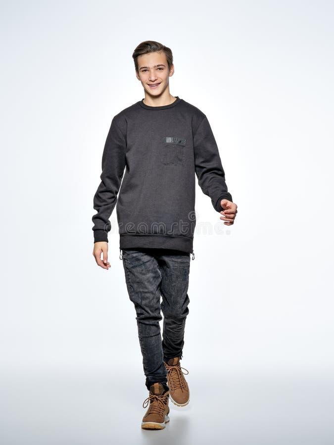 Gladlynt iklädd svart moderiktig kläder för tonårs- pojke som poserar på s royaltyfria foton