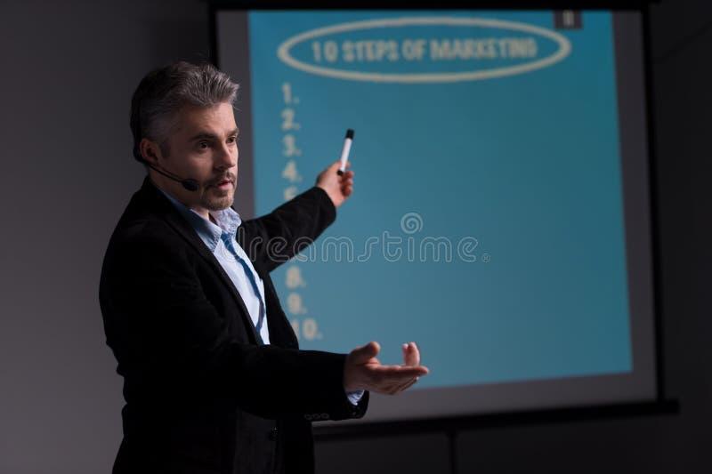 Gladlynt instruktör som pekar på skärmen med presentation royaltyfria bilder