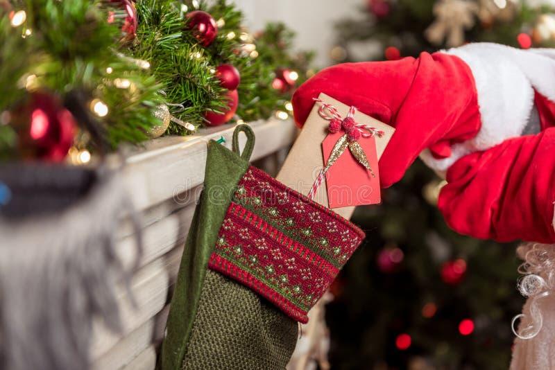 Gladlynt jultomten som döljer gåvan i stansmaskin arkivfoto