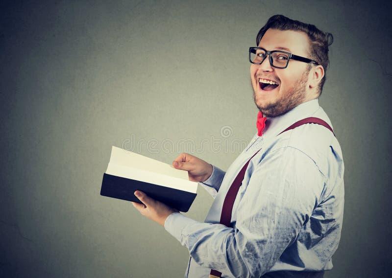 Gladlynt knubbig man med boken royaltyfri bild