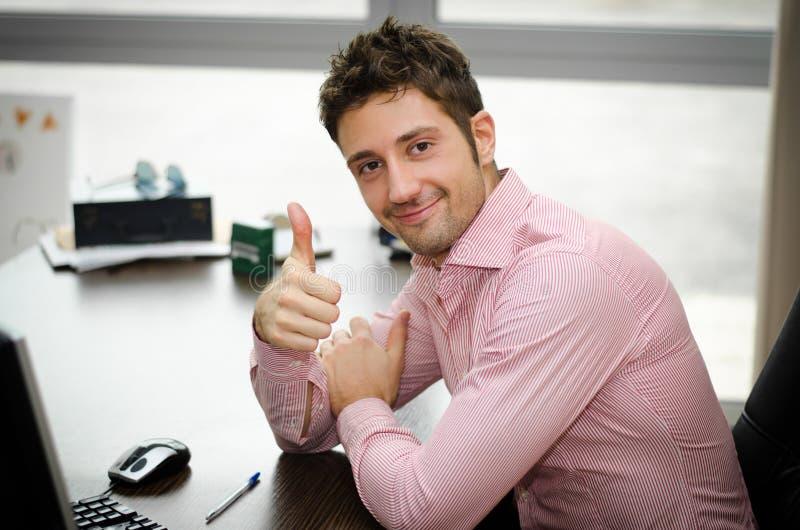 Gladlynt kontorsarbetare på skrivbordet som gör tummen upp tecken och att le royaltyfri bild