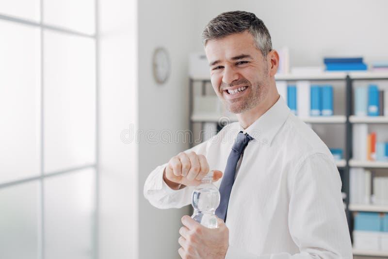 Gladlynt kontorsarbetare som rymmer en vattenflaska arkivbilder
