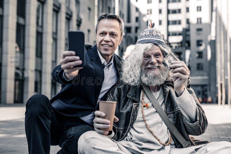 Gladlynt kort-haired affärsman som gör fotoet med att stråla hemlöns royaltyfria bilder