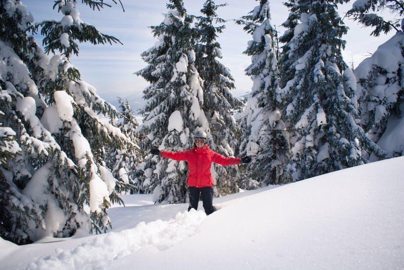 Gladlynt kvinna bland granträd i snön arkivfoto