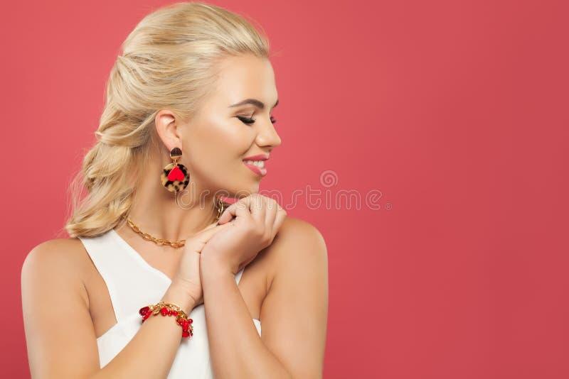 Gladlynt kvinna i guld- smyckeörhängen för mode med det röda hjärta- och korallarmbandet på rosa bakgrund med kopieringsutrymme arkivfoto