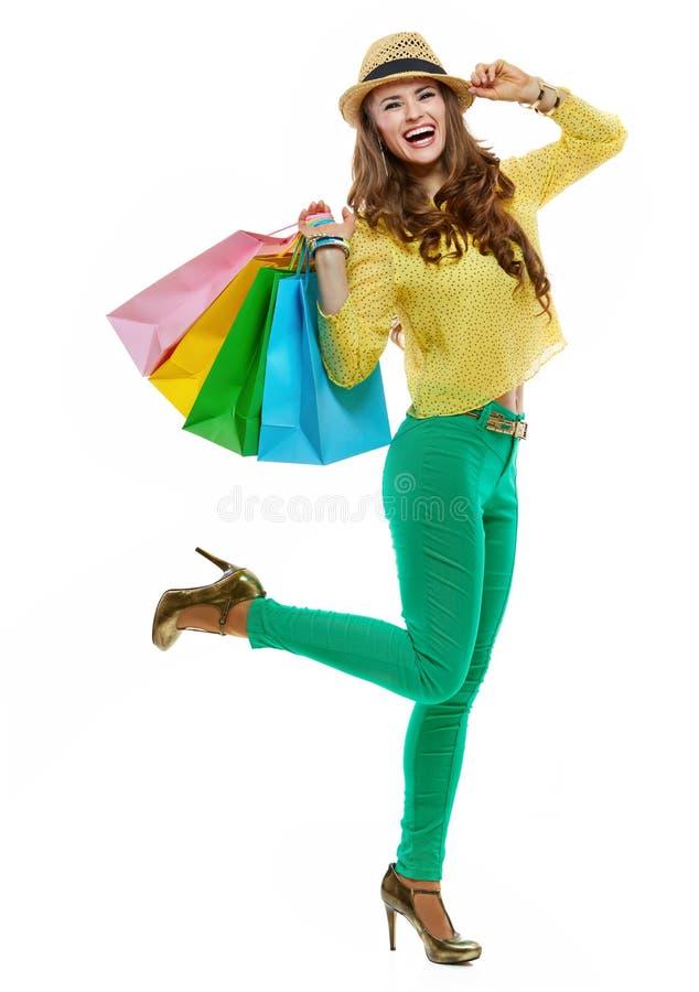 Gladlynt kvinna i hatt och ljus kläder med shoppingpåsar arkivfoton