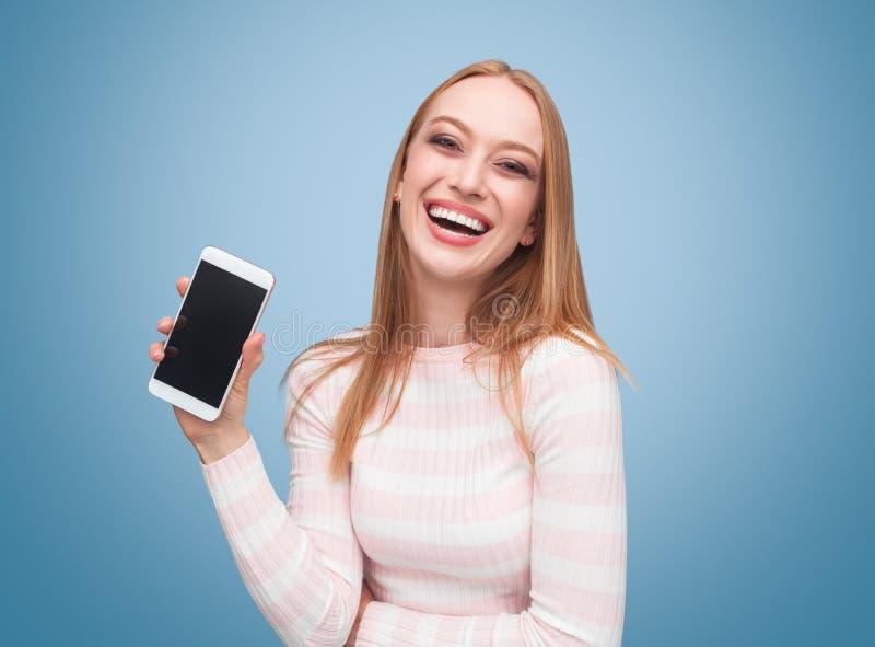 Gladlynt kvinna med den nya smartphonen royaltyfri foto