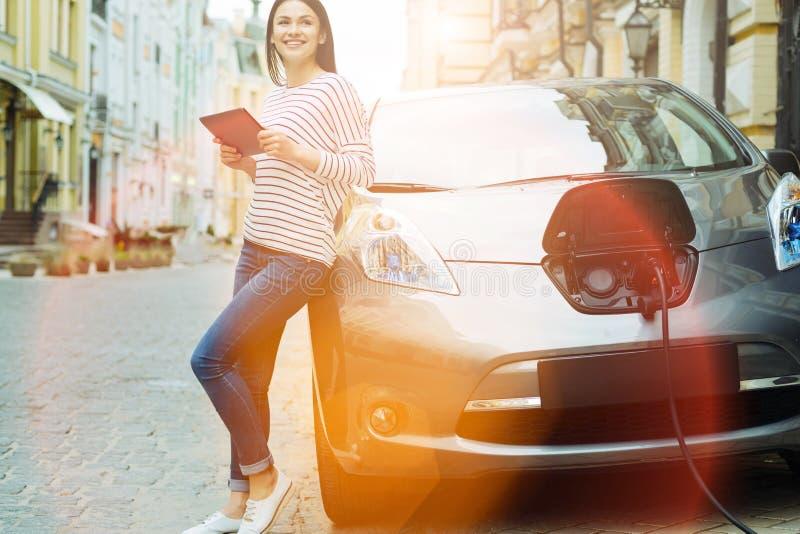 Gladlynt kvinna med en minnestavlabenägenhet på hennes bil royaltyfri foto