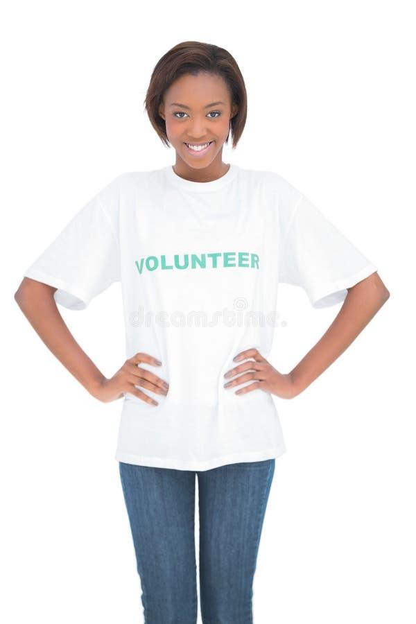 Gladlynt kvinna med händer på höfter som bär volontärtshirten arkivbilder