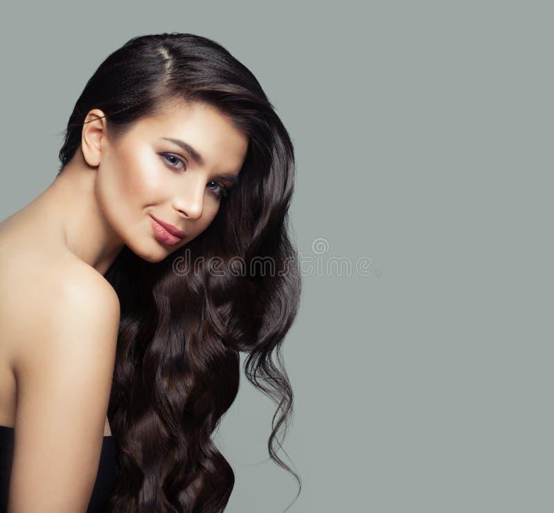 Gladlynt kvinna med salongbakgrund för mörkt brunt lockigt hår, haircare- och skönhet fotografering för bildbyråer