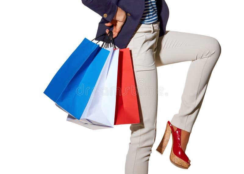Gladlynt kvinna med shoppingpåsar i solglasögon på vit arkivbild