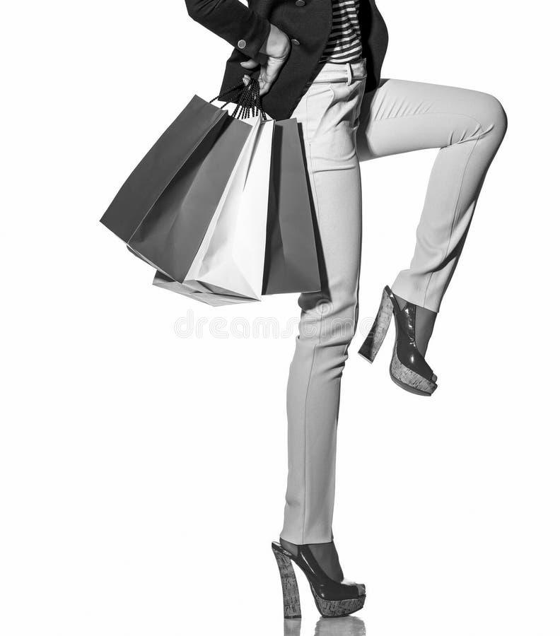 Gladlynt kvinna med shoppingpåsar i solglasögon på vit royaltyfri bild