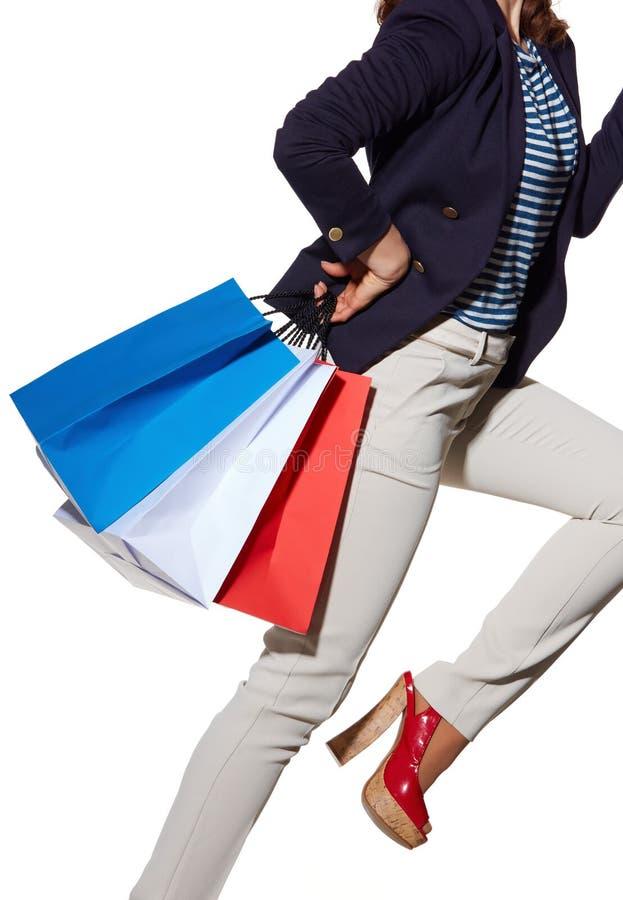 Gladlynt kvinna med shoppingpåsar i solglasögon på vit arkivfoton