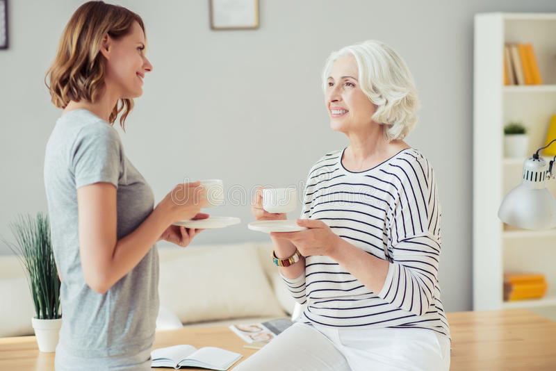 Gladlynt kvinna och hennes vuxen dotter som dricker te royaltyfria bilder