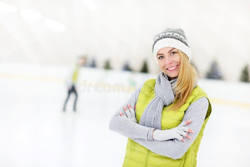 Gladlynt kvinna på en åka skridskor isbana fotografering för bildbyråer