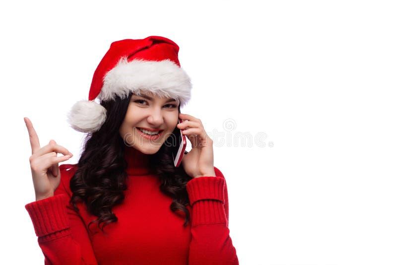 Gladlynt kvinna som bär den santa hatten med det gick ut fingret för framsidauttrycksvisning upp och talar på telefonen som isole arkivbilder