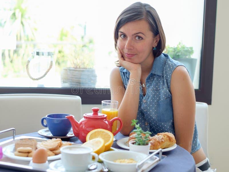 Gladlynt kvinna som har en kontinental frukost fotografering för bildbyråer