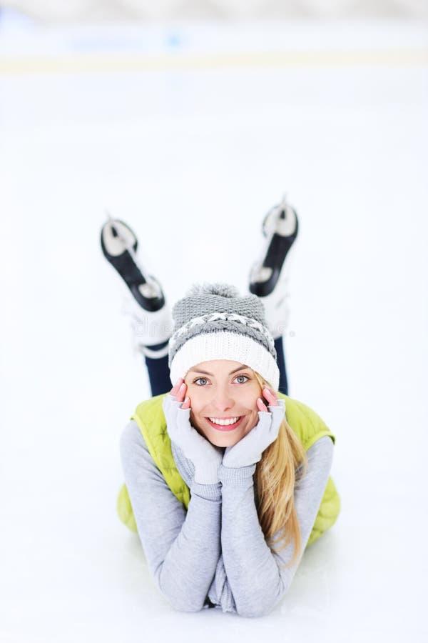 Gladlynt kvinna som ligger på en åka skridskor isbana royaltyfria bilder