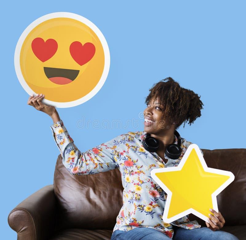 Gladlynt kvinna som rymmer en hjärtaögonemoticon och stjärnasymboler fotografering för bildbyråer