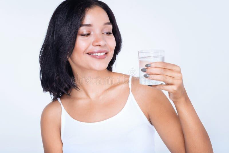 Gladlynt kvinna som rymmer ett exponeringsglas av vatten arkivbild