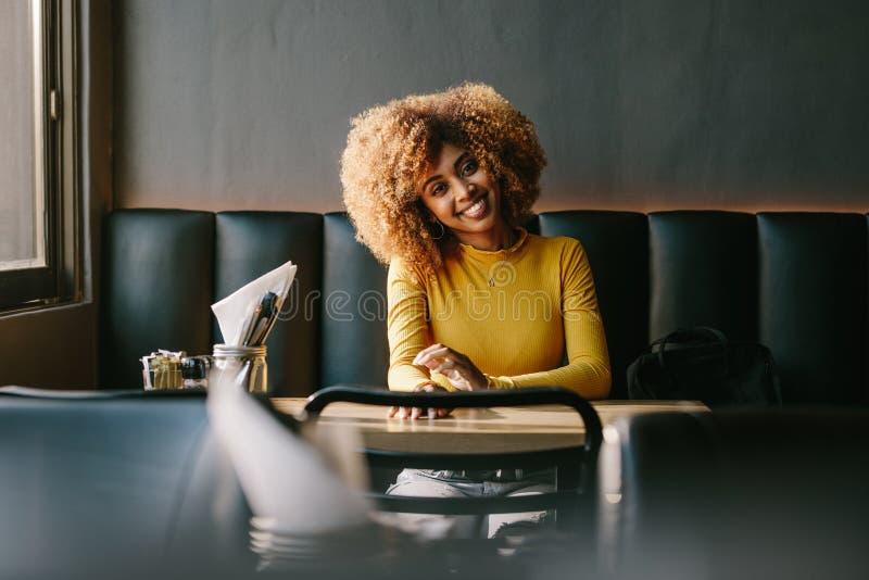 Gladlynt kvinna som sitter i en restaurang arkivfoton