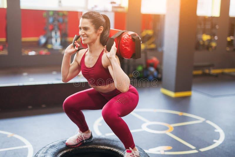 Gladlynt kvinna som squatting med påsen arkivfoto