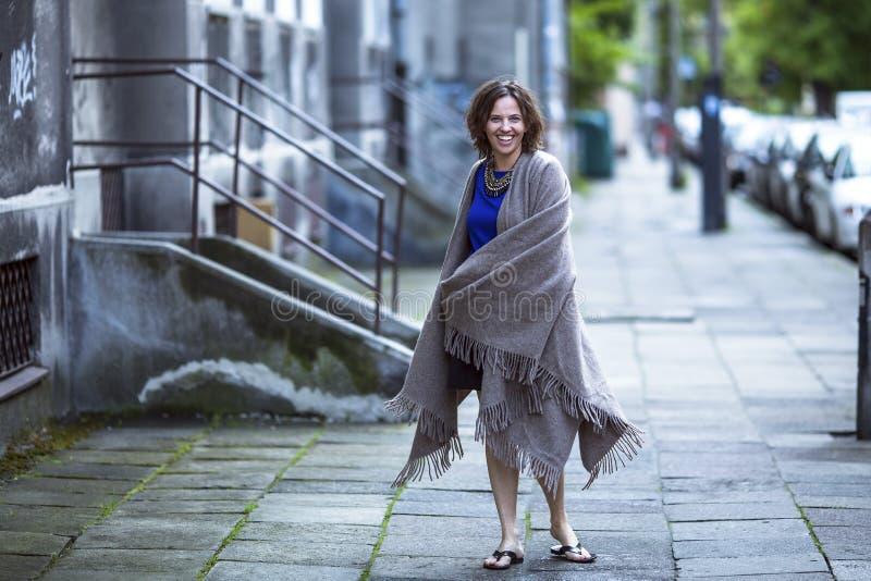 Gladlynt kvinna utomhus på aftontid i staden royaltyfria bilder