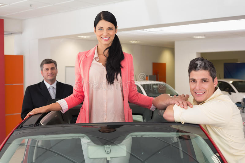 Gladlynt kvinnaanseende i röd cabriolet arkivbild