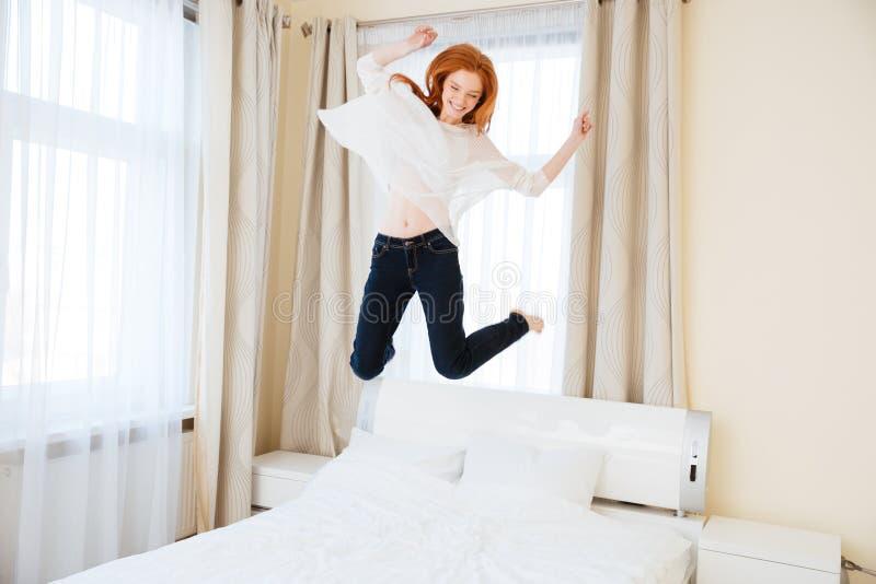 Gladlynt kvinnabanhoppning på sängen arkivbilder