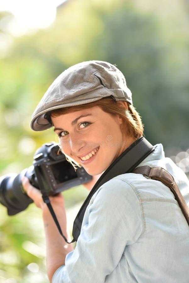 Gladlynt kvinnafotograf på arbete arkivbilder