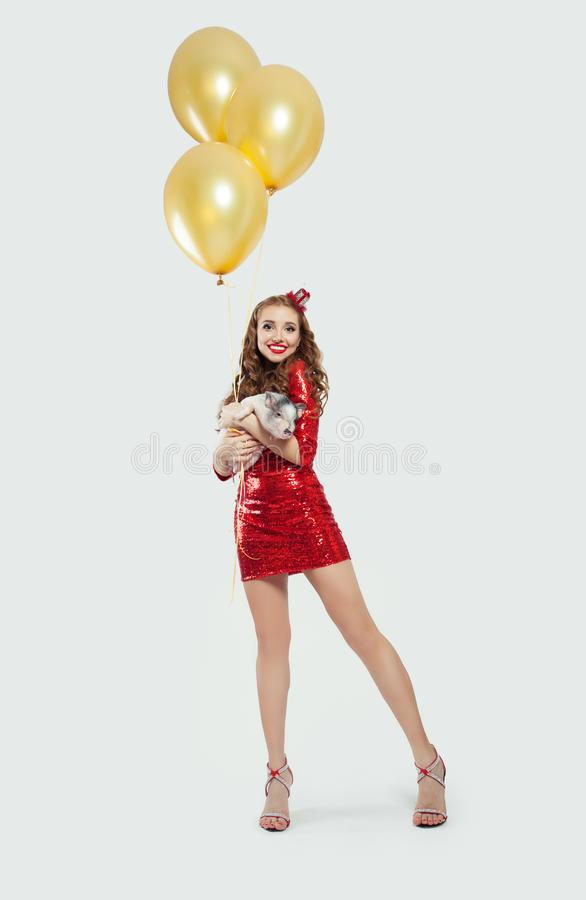 Gladlynt kvinnamodemodell i röd partiklänning med det lilla svinet och gula ballonger på vit bakgrund royaltyfria bilder