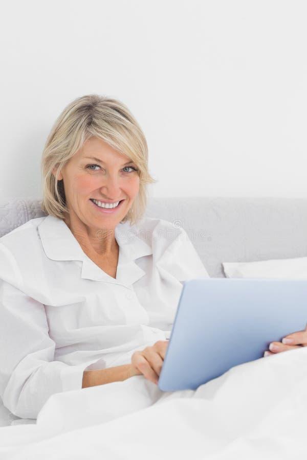 Gladlynt kvinnasammanträde i säng genom att använda minnestavlaPC:n som ser kameran arkivfoton
