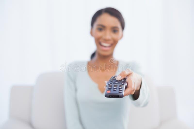 Gladlynt kvinnasammanträde på den ändrande TV-kanal för soffa royaltyfria foton