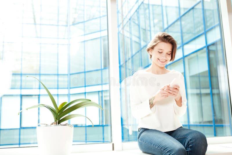 Gladlynt kvinnasammanträde på fönsterbräda i regeringsställning och genom att använda smartphonen fotografering för bildbyråer