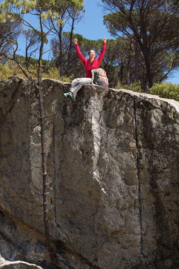 Gladlynt kvinnasammanträde på kanten av berget med lyftta händer royaltyfri bild