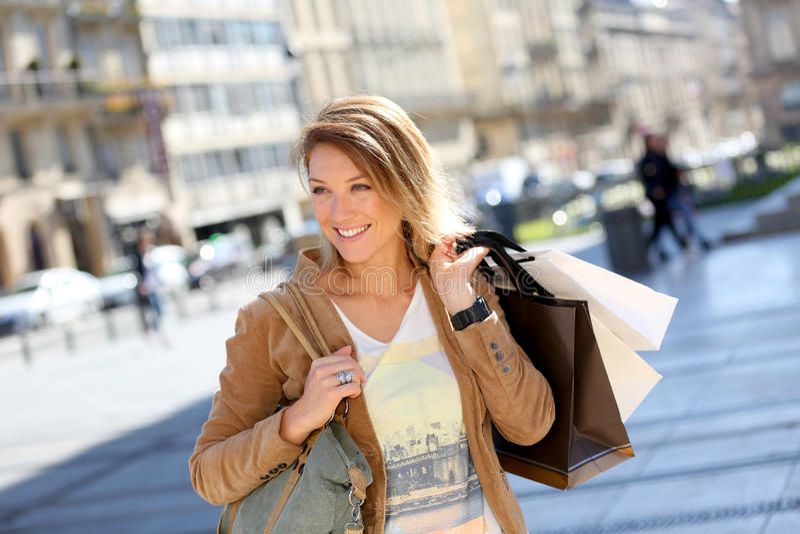 Gladlynt kvinnashopping på försäljningar i gatorna royaltyfri bild