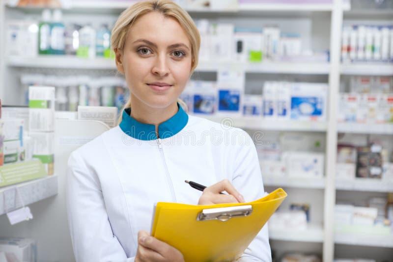 Gladlynt kvinnlig apotekare som arbetar på apoteket arkivbild