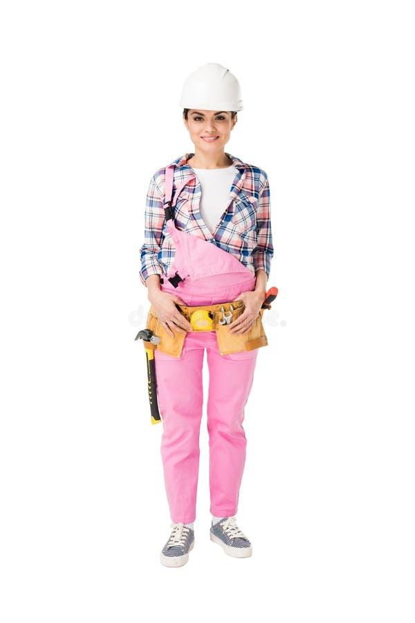 Gladlynt kvinnlig byggnadsarbetare i rosa likformig royaltyfri bild