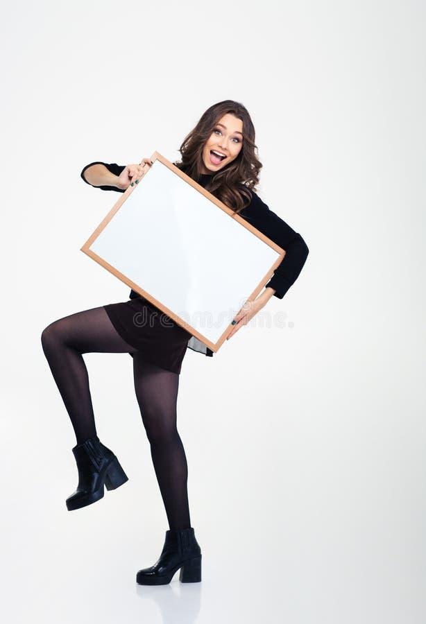 Gladlynt kvinnlig flicka som poserar med det tomma brädet fotografering för bildbyråer
