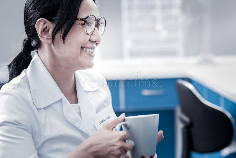 Gladlynt kvinnlig forskare som tar avbrottet och dricker kaffe royaltyfria foton