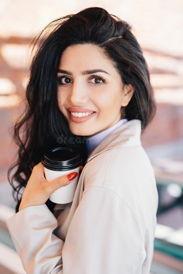 Gladlynt kvinnlig med den älskvärda appearncen för mörkt hår som rymmer takeawayen royaltyfria bilder