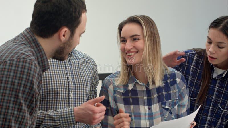 Gladlynt lag av teknikerer som tillsammans arbetar i arkitektstudio royaltyfri foto